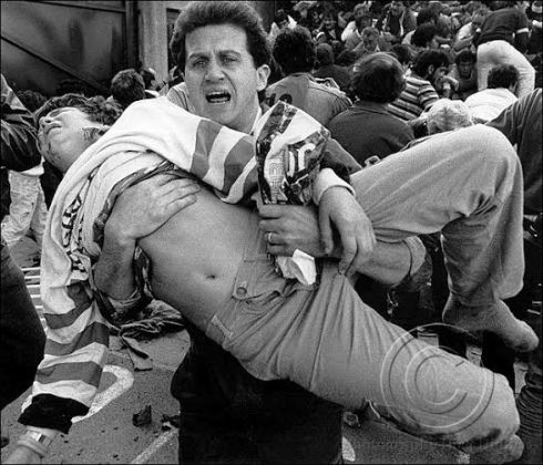 Brussels, Belgium: A man carries his injured child from the collapsed stands of Heysel Stadium during a soccer riot before the start of the 1984 the European Cup football final.The rioting lead to the collapse of a retaining wall and in the panic that ensued many people were trampled or crushed, resulting in the death of 39 people